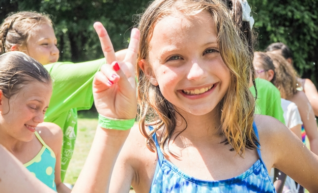 A girl flashes the peace sign while smiling during a retreat.