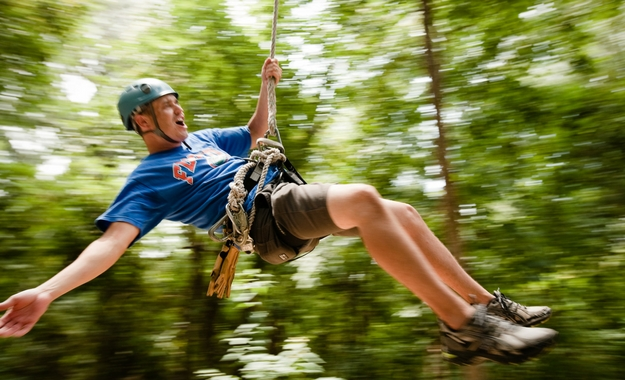 A man swings through the trees on a zip line at Camp Canaan's Zip Line Canopy Tour