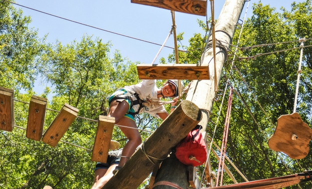 A counselor smiles through the wooden walking planks of the ropes course.