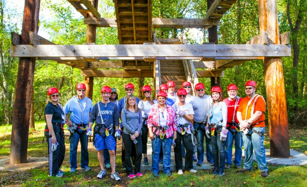 A group of company employees stand in front of a tower and pose for a picture before beginning the zip line course.