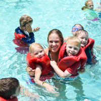 A female camp counselor holds two girls in the swimming pool. Each girl is wearing a red life jacket.