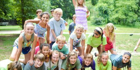 A group of campers build a pyramid.