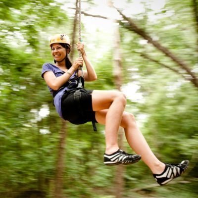 A lady swings through the trees on the zip line canopy tour.