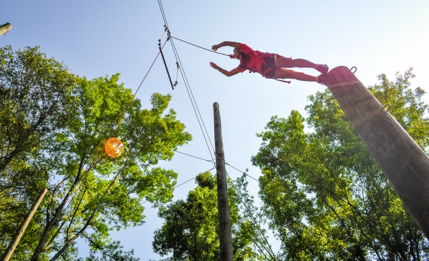 "A young girl makes the ""Leap of Faith"" jump on the high ropes course at Camp Canaan."