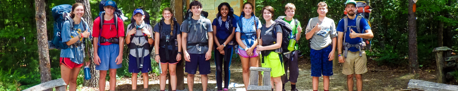 A group of teens pose in front of a trail sign before going hiking.