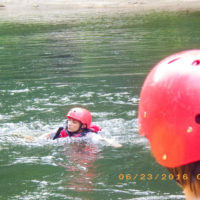 A teen wearing a red helmet swims in the river after falling out of the raft.
