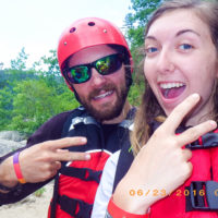 A counselor and a female teenager give the peace sign. Each are wearing life jackets.