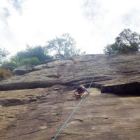 A teenager climbing up a rock face using ropes and a harness.