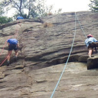 Two teens scale a cliff face by climbing up some ropes.