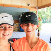 Two girls wearing Nike running hats pose for a photo together.