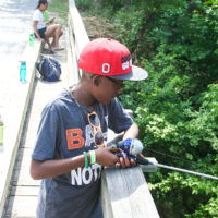 A young boy wearing a red baseball hat leans over the wooden rail of a bridge fishing.