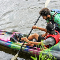 A counselor gives some kayak instruction to a camper in the river.