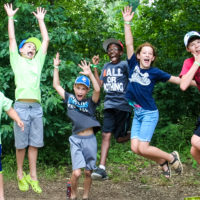 A group of kids leap in the air with crazy faces posing for the camera!