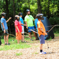 A boy wears a protective face mask and awaits his turn to shoot in a game of archery tag.