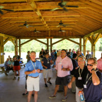 A group of adults during a corporate retreat chat under an outdoor shelter an sunny day.