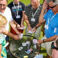 A group of adults stand in a circle around a table as a magician performs card tricks.