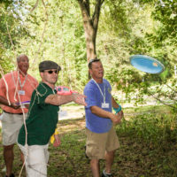 Three guys tee off on Camp Canaan's disc golf course.