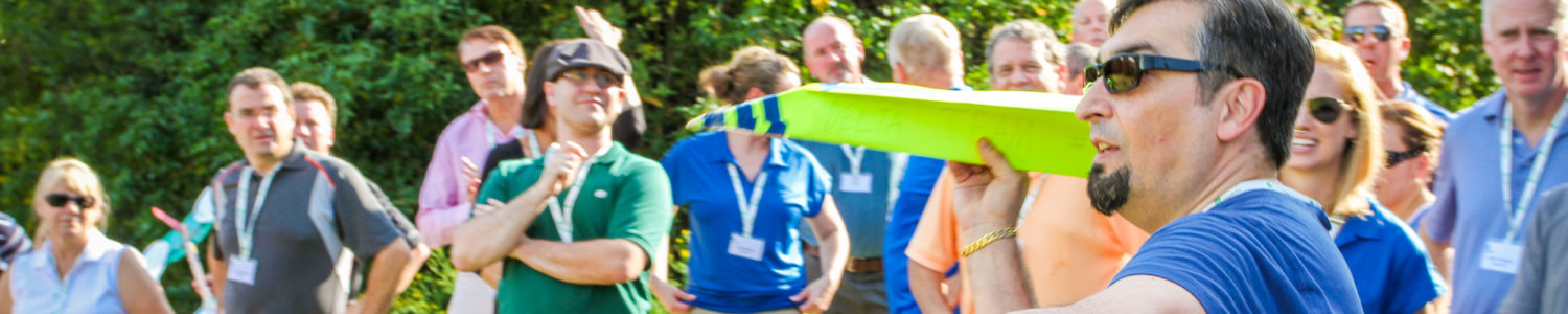 A group gathers around as a man prepares to launch a lime green cardboard airplane.