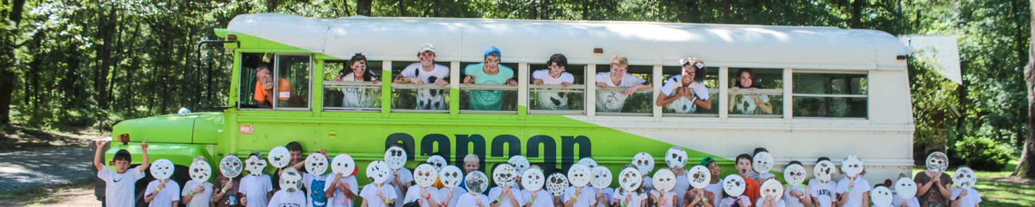 Kids pose in front of and in the bright Camp Canaan bus.