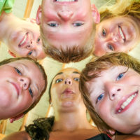 A group of kids put their heads together and look down at the camera.