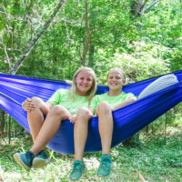 Two girls pose in an Eno hammock during an Island Escape camp at Camp Canaan.