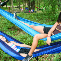 Two girls lay in their hammocks smiling.