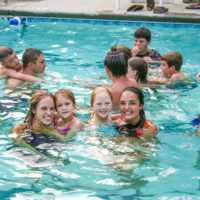 Two young campers pose in the pool with two counselors.