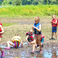 Kids wearing life jackets play in the mud on the bank of the river.