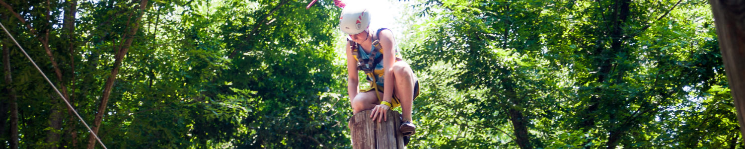 A senior camper climbs on top of a high post on the high ropes course.