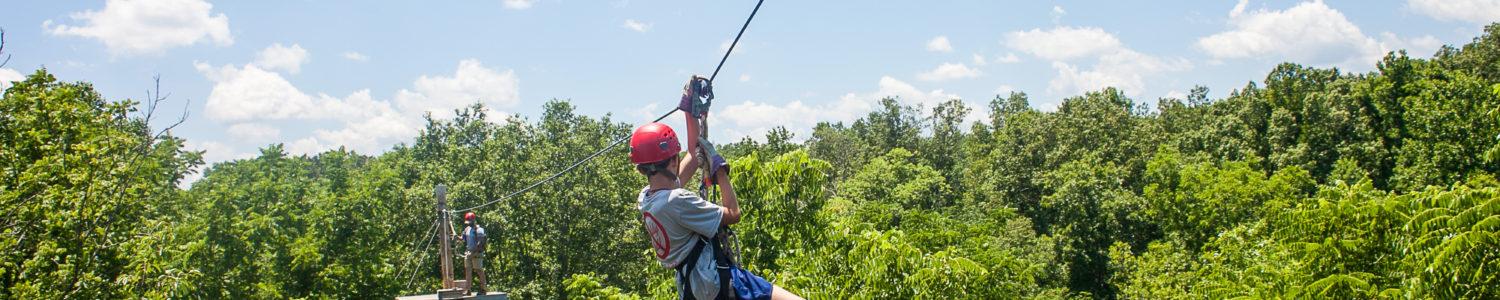 A kid zip lining across a gorge.