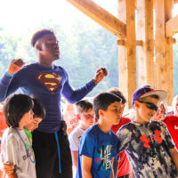A counselor wearing a Superman tee shirt talks excitedly to some campers.