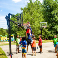 A counselor lifts up a young boy to allow him to dunk a basketball.