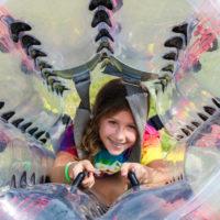 A young girl sticks her head through a bubble soccer ball.