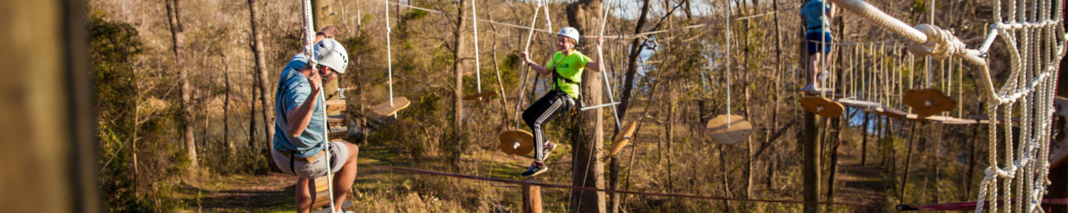 Two people balance on the high ropes course at Camp Canaan.