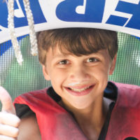 A young boy smiles while holding a water tube over his head.