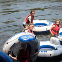 A group of kids put their tubes in the river before going tubing.
