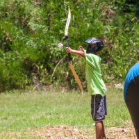 A boy in a lime green shirt prepares to shoot an arrow during a game of archery tag.