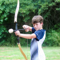 A boy in a blue and white shirt prepares to shoot an arrow during a game of archery tag.
