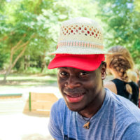 A camp counselor smiles while wearing a straw hat on top of his red baseball cap.