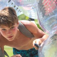 A young boy climbs through a bubble soccer ball.