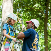 A counselor helps a young girl get prepared to do the ropes course.