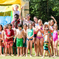 A group of kids pose for a picture after playing on an inflatable water slide.