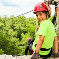 A young boy sits on top of a platform smiling. He's about to go ziplining.