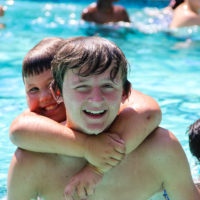 Two young boys smile for a picture while swimming in the pool.