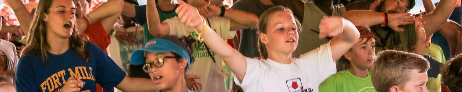 A group of kids dance and sing at Camp Canaan