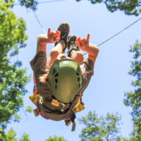 A young boy zip lining.