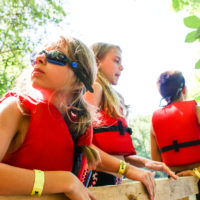 Three girls in life jackets getting ready to go in the river.