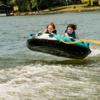 Two girls holding on tightly to an inflatable tube being pulled behind a boat.
