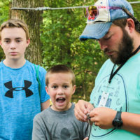 A camp counselor puts bait on a hook for a camper.