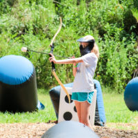 A girl draws back her bow while playing a game of archery tag.
